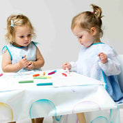 Girls drawing at table covered in messy mat