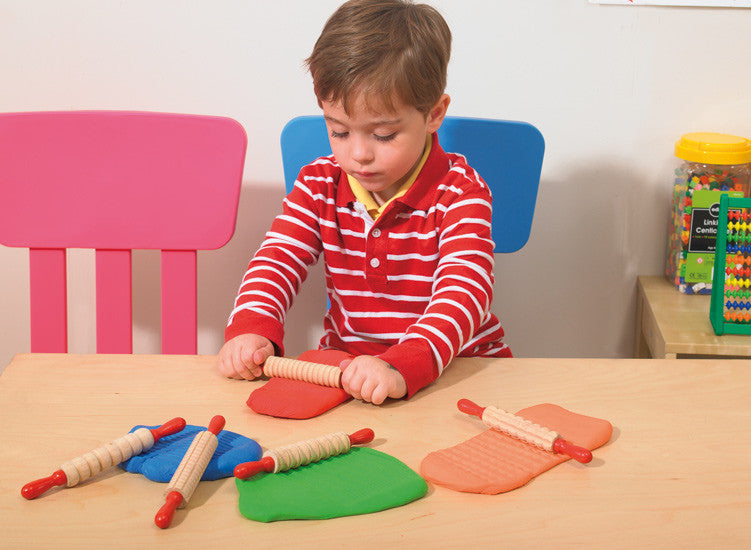 Boy rolling playdough with patterned rolling pin