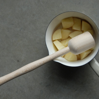 masher shown with potato in saucepan