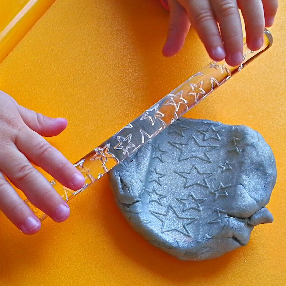 hands rolling star patterns with rolling pin and silver pearl dough