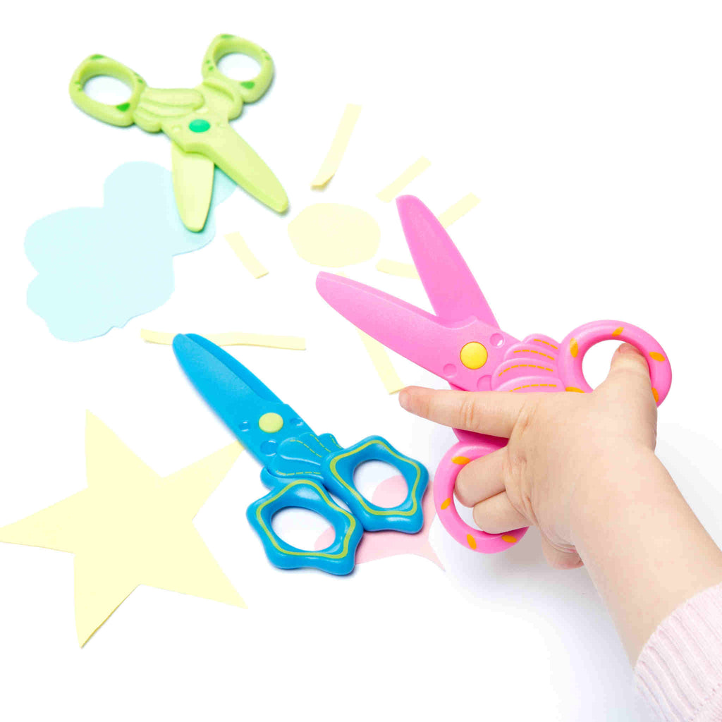 child's hands shown with pink scissors. Blue and green scissors also shown