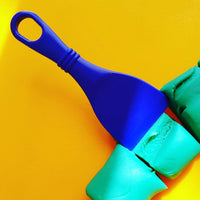 blue slicer shown in green playdough on a yellow table