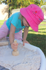 girl playing with wooden stamper in sand