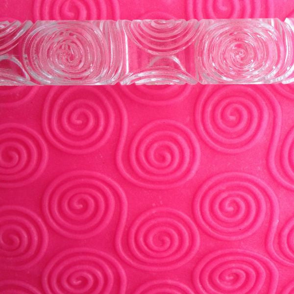 rolling pin with swirly patterns in pink playdough