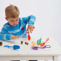 child playing with rainbow tongs