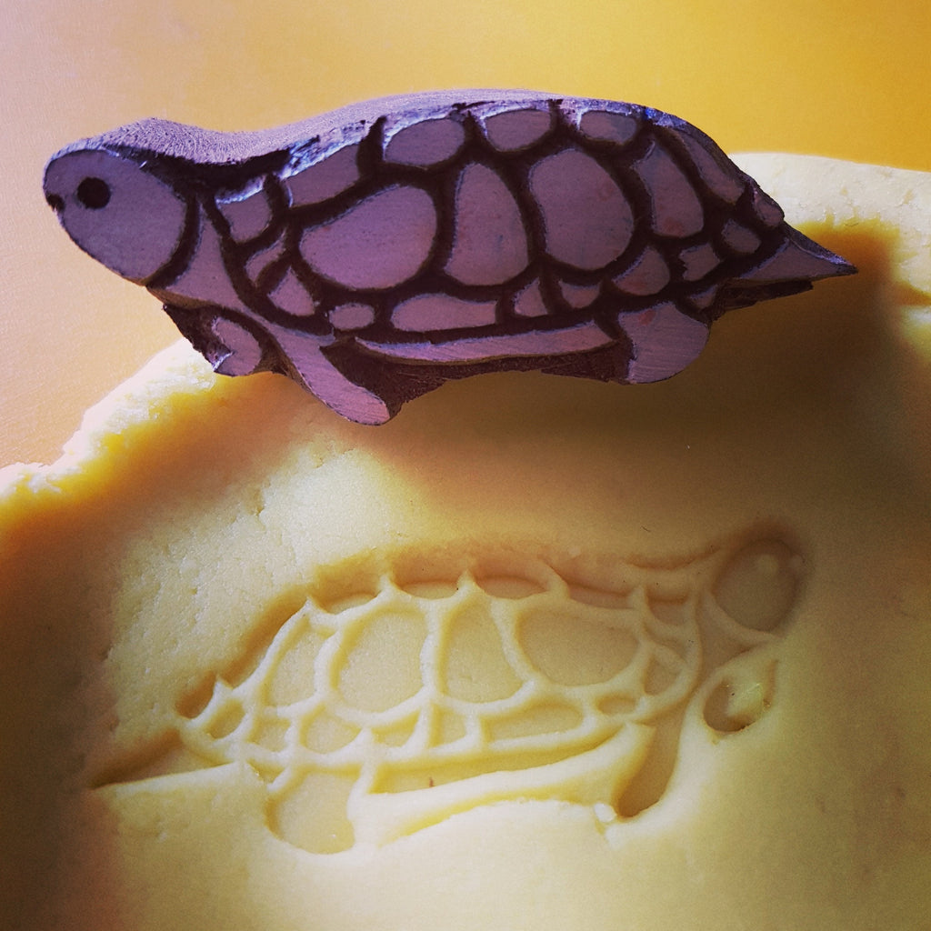 Wooden turtle stamp with yellow playdough