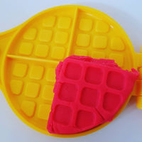 yellow waffle iron shown with red playdough