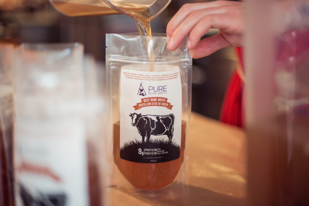Pure Bone Broth being poured into a plastic package