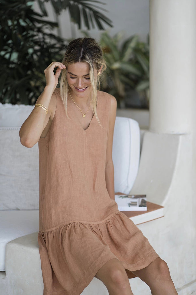 Humidity Ruby Dress is the perfect summer throw on in a garment dyed French linen that is perfect for the hot weather. The flattering v-neckline suits any bust size, and the length comes to the knee on most (the model is 6').  100% Linen Cool gentle hand wash in mild detergent for best care