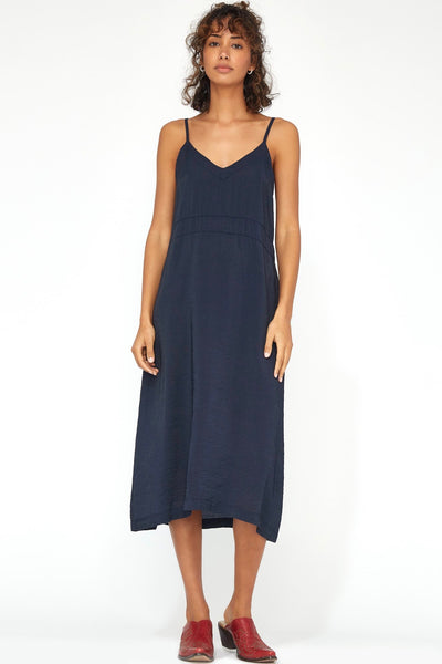Lacausa Alma Slip Dress is a simple, loose fitting style with thin, spaghetti straps that falls to below the knees. The dress has a flattering V-neck shape in the front, and the back goes straight across above the bra line. This dress can be worn on it's own or layered under something sheer.  84% Rayon 16% Nylon Cool gentle hand or machine wash, dry flat Made in Los Angeles, USA