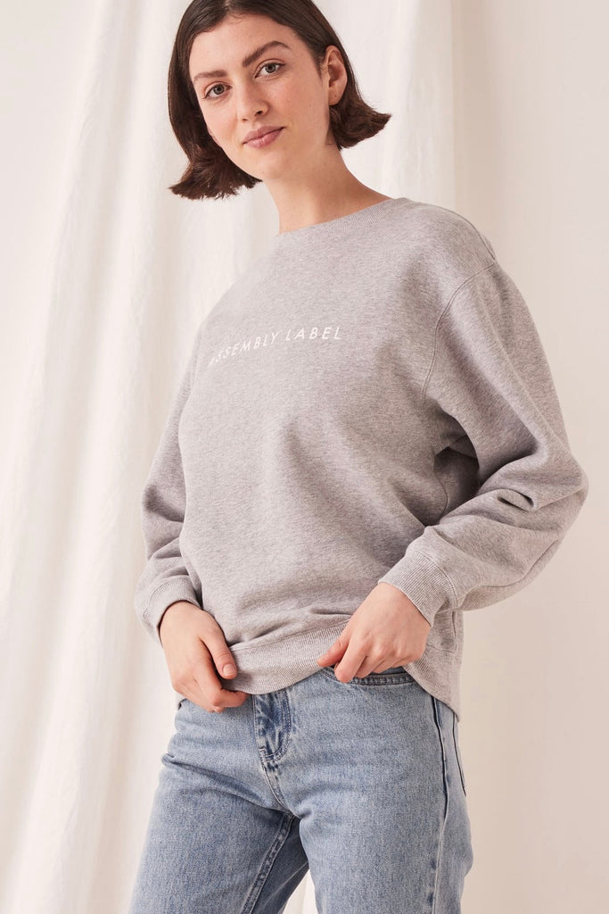 "Assembly Label Logo Fleece in Grey Marle is an understated crew neck wind-cheater made from a premium cotton fleece. This long sleeve, hip length style has a super soft interior and features the ""Assembly Label"" logo on the front in white.  100% Cotton Cool gentle machine wash"