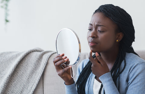woman looking in the mirror concerned and touching her face.