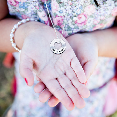 woman holding blessing ring on necklace in hand