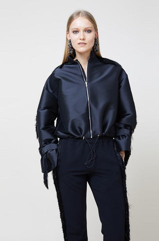 """Evening bomber jacket with side pockets, puff sleeves and ruff collar. Metal zipper at front and sporty drawstring. Sleeves trimmed with black fringe. """"It extenuates my petite frame and the fringe adds such a unique touch!"""" -Aoife Curly, PR Coordinator Fabric: Jet satin stretch jacquard"""