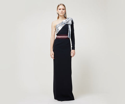"""One-sleeve crepe column gown with silver sequined draped bow. Waist is accentuated with multicolor grosgrain. """"Dress for the red carpet even if it's just your cousins wedding."""" -Emily Jacobs, VP of Sales Fabric: Jet stretch crepe with silver sequins. <!-- td {border: 1px solid #ccc;}br {mso-data-placement:same-cell;} --><!-- td {border: 1px solid #ccc;}br {mso-data-placement:same-cell;} -->"""
