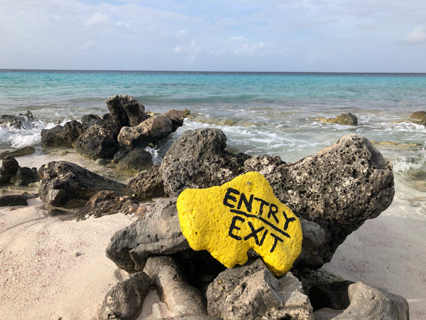 Painted rocks marking the entry and exit points of a shore dive in Bonaire