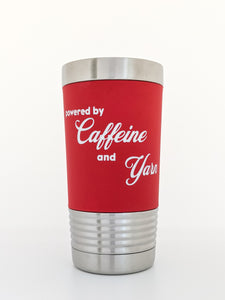 "Image shows a stainless steel tumbler wrapped with a removable silicone sleeve that has been laser engraved with the phrase ""Powered by Caffeine and Yarn"" in white letters on a red background."