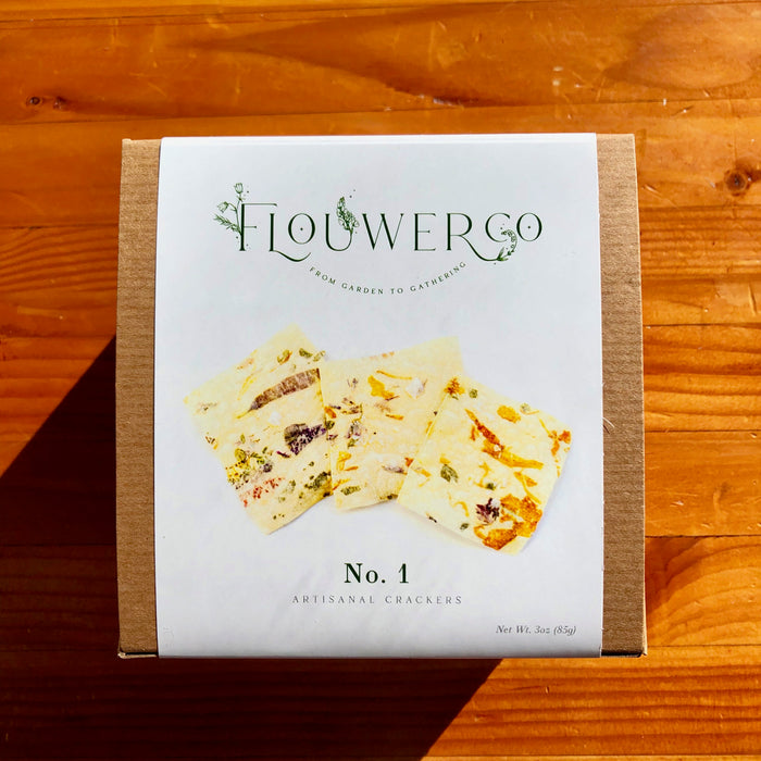 A box of Flouwer Co Flower and Herb Infused Crackers, thin luxury crackers with visible flowers and herbs baked inside