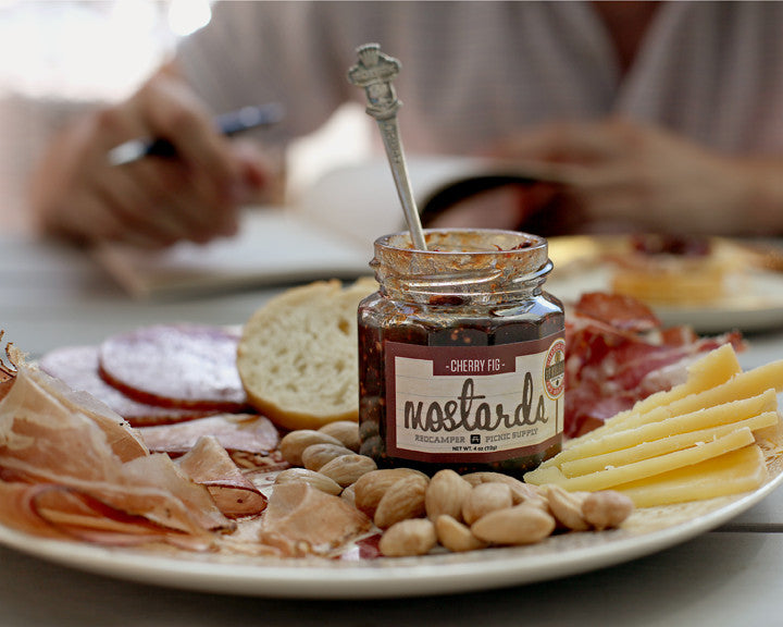 Jar RedCamper Cherry Fig Mostarda on charcuterie board with cured meats, cheeses bread and nuts Picnic Supply