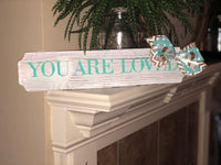 "White wood ""You are loved"" sign"