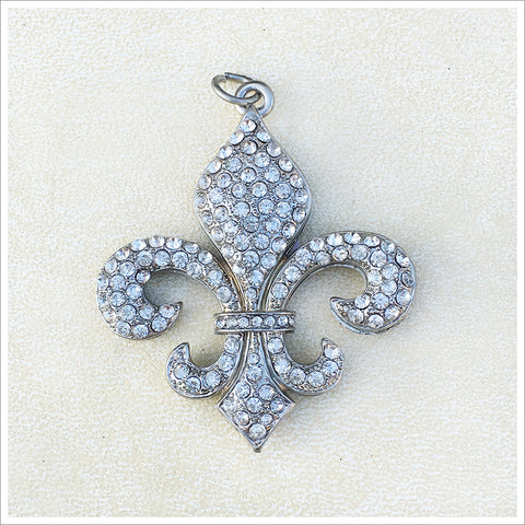 Stunning fleur-de-lis pendant, cast in a silver finish and encrusted with sparkly rhinestones.