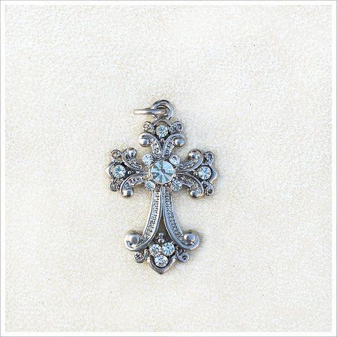 Lovely, small cross pendant or bracelet charm, cast in a silver finish and encrusted with sparkly rhinestones.