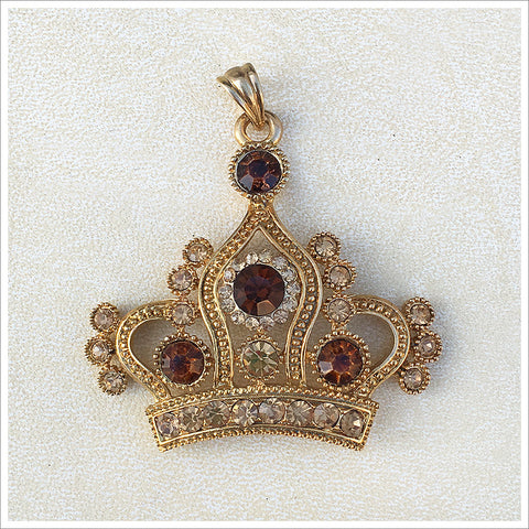 Large crown pendant, cast in a gold finish and encrusted with topaz and smoky topaz rhinestones.