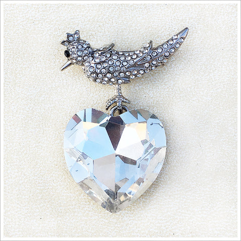 Very unusual bird and heart pendant, cast in a silver finish and encrusted with sparkly rhinestones.