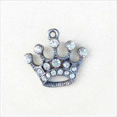Whimsical, small crown pendant or charm, cast in an antiqued silver finish and encrusted with sparkly rhinestones.