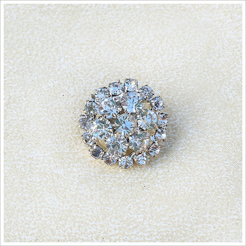 Small rhinestone button, featuring many prong-set stones in a silvery setting.