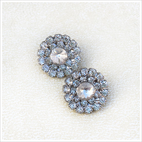 Set of two small rhinestone buttons, featuring many prong-set stones in a silvery setting.