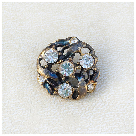Vintage rhinestone button in an antiqued gold setting.