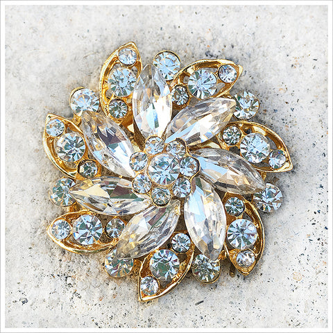 Gorgeous vintage brooch featuring marquis and round rhinestones in a golden setting.