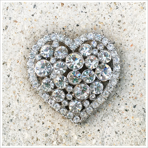 Lovely, classic heart brooch. Cast in a silver-toned setting and covered in rhinestones.