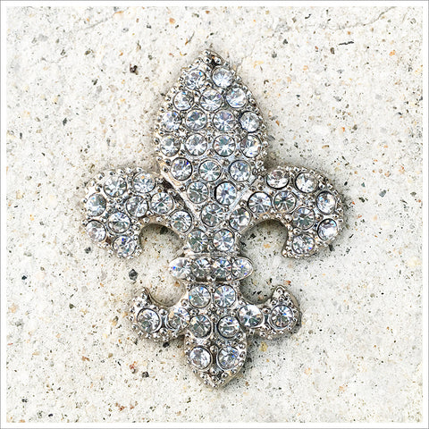 Lovely, classic fleur de lis brooch. Cast in a silver-toned setting and covered in rhinestones.