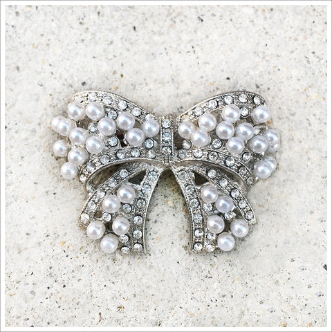 Such a unique and pretty rhinestone and pearl brooch. Cast in a silver-toned bow shaped setting!