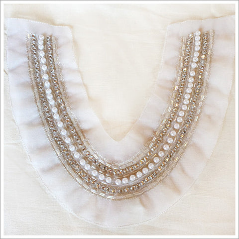 Ivory tulle, heavily encrusted with pearls and clear, silver-lined bugle beads.  Meant to be sewn around the neckline of a dress, top or t-shirt.