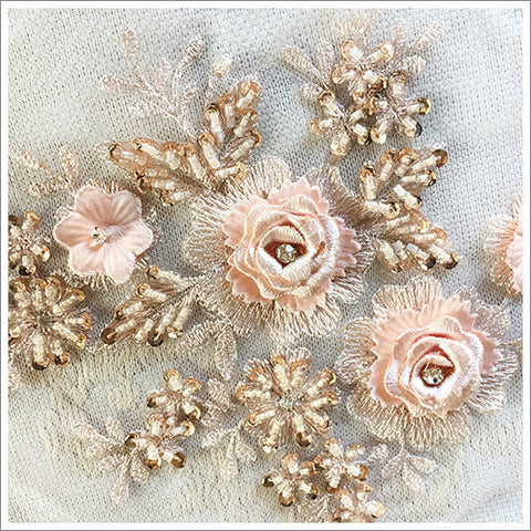 Detail of appliqué featuring embroidered roses, beads, and rhinestones.