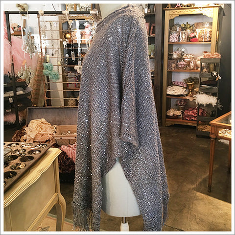 A classic poncho shape in the softest acrylic knit. A gorgeous gray, transformed with silver metallic yarn and lush fringe.