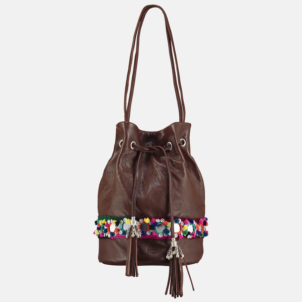 small brown  leather bucket bag with colourful pom pom mirror belt detail and metallic tassles
