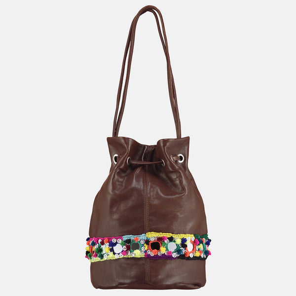 small veg tan leather bucket bag with mirror handwork tribal detail bright pompoms . rear view
