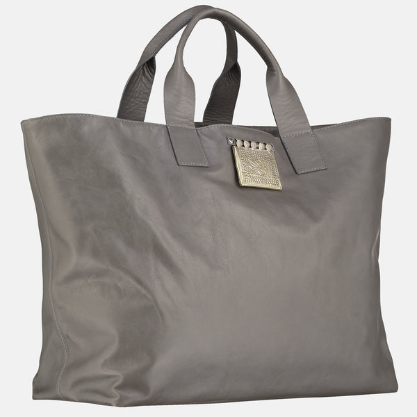 grey italian leather handmade travel bag. leather tote , side view , silver colour tribal pendant detail