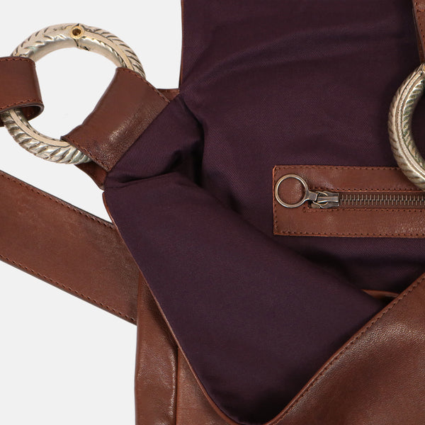 close up interior zip pocket handmade brown leather cross body shoulder bag . close up vintage tribal jewellery bracelet