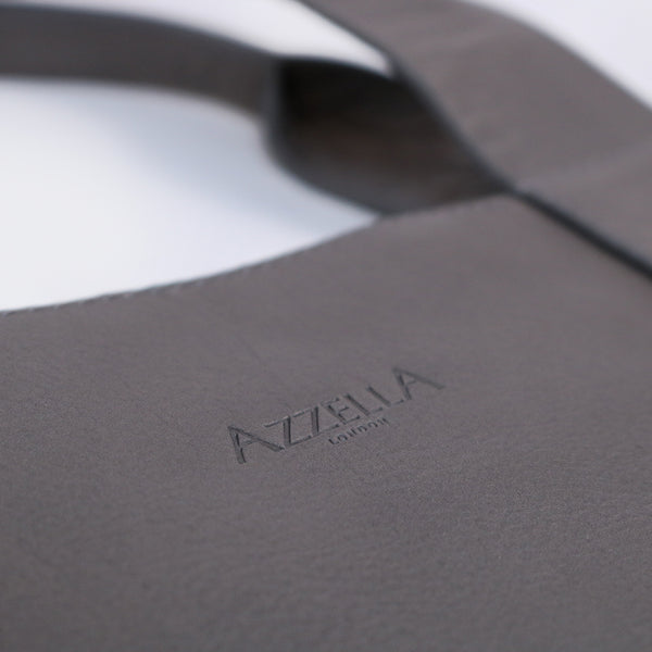 close up detail of azzella logo on italian leather grey handmade bag artisan