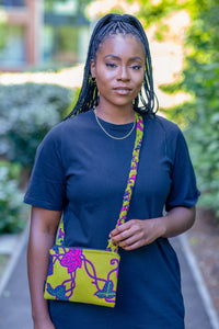 beautiful black woman wearing black dress and african print clutch bag