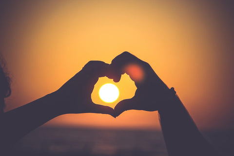 Two hands making a heart over the sun