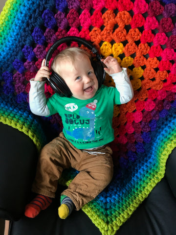 Elliott sits on a black chair, wearing head phones, on a chunky rainbow crochet blanket