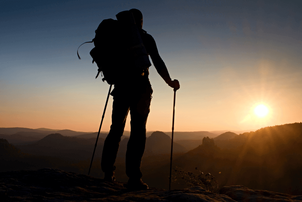 man with trekking poles on mountain