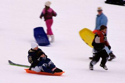 Children sledding down a hill quickly