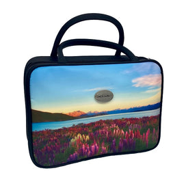 A rectangular vanity/cosmetic case with 2 black handles. The front and back of the cosmetic case display a beautiful scene of pink and purple lupins, with New Zealand's spectacular mountain ranges in the background, under a blue sky with wispy clouds. One side of the cosmetic case also features a silver badge with the AA Traveller logo. The sides are black, with a black zip around 3 sides.